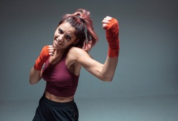 Pretty girl fighter in boxing bandages makes an uppercut in studio isolated on gray background. Strength and motivation