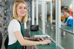 Pretty girl handles manual work in the factory