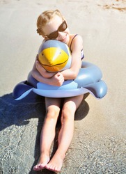 Pretty girl has fun on beach with rubber duck