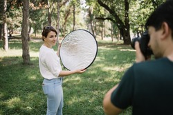 Pretty girl having a photo session while holding reflector. Out of focus photographer taking pictures of girl who is holding silver reflector.