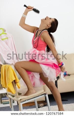 Pretty girl having fun at home, singing, posing, laughing.