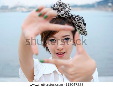 Pretty girl having fun outdoor, making frame with hands, taking picture with imaginary camera, selective focus