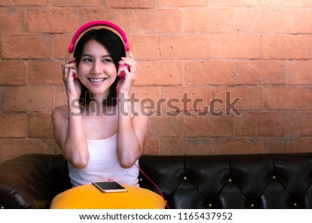 Pretty girl hear song from her headphone. She is dozing on a sofa.