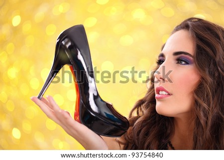 pretty girl holding a black high heel shoe in her hand and looking at it