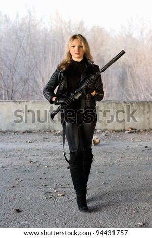 Pretty girl holding a gun in neglected building