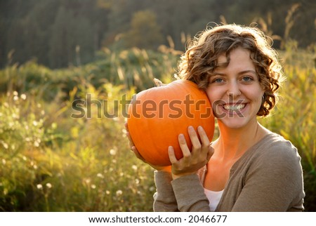Pretty girl holding a pumpkin to her cheek