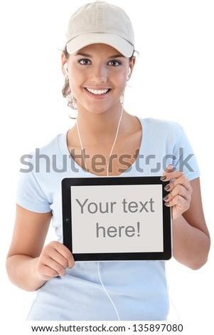 Pretty girl holding tablet with blank screen, smiling.