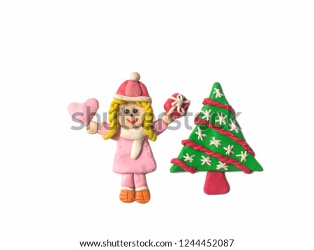 Pretty girl holding the pink heart and red gift box and cute Christmas tree made from plasticine clay placed on white background, cute child dough wearing a coat in winter festival #1244452087