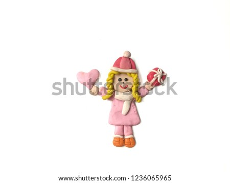 Pretty girl holding the pink heart and red gift box made from plasticine clay placed on white background, cute child dough wearing a coat in winter festival #1236065965
