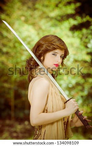 Pretty girl in a dress with vintage sword outdoors