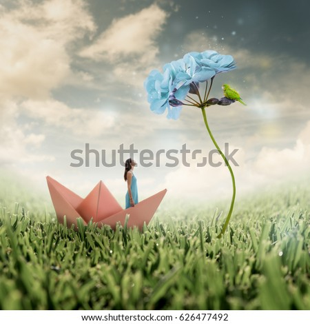 Stock Photo Pretty girl in a pastel colored dress looking up to an enlarged bright blue flower with a green parrot