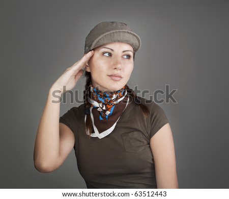 Pretty girl in cap saluting