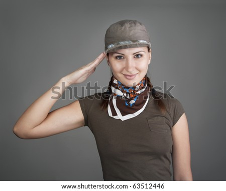Pretty girl in cap saluting