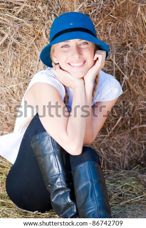 Pretty girl in checked shirt resting on straw bale