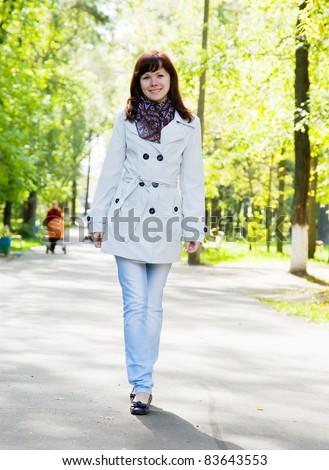 Pretty girl in cloak walking outdoors in autumn