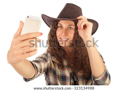 Pretty girl in cowboy style making selfie on her smart phone.