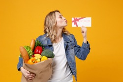 Pretty girl in denim clothes isolated on orange background. Delivery service from shop or restaurant concept Hold brown craft paper bag for takeaway mock up with food product kissing gift certificate