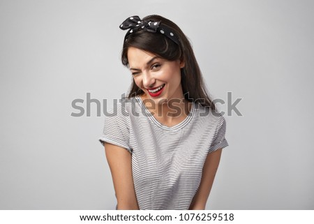 Stock Photo Pretty girl in her twenties winking at camera, smiling playfully. Studio shot of coquettish young brunette woman with bright make up blinking, looking at you with mysterious smile, flirting