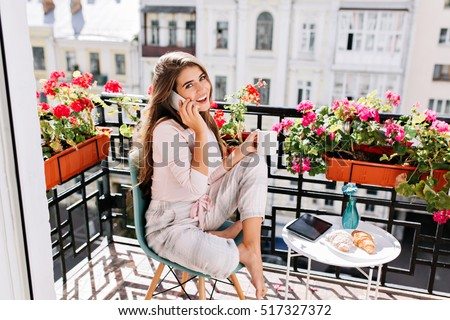 Pretty girl in pajama having breakfast on balcony in the sunny morning. She holds a cup, speaking on phone smiling to camera