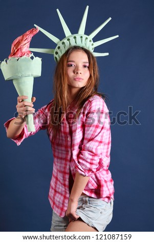 Pretty girl in pink shirt with crown and torch represents statue of liberty.