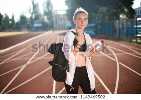 Stock Photo Pretty girl in sport wear dreamily looking in camera with backpack on shoulder and bottle of pure water in hand on running track of stadium