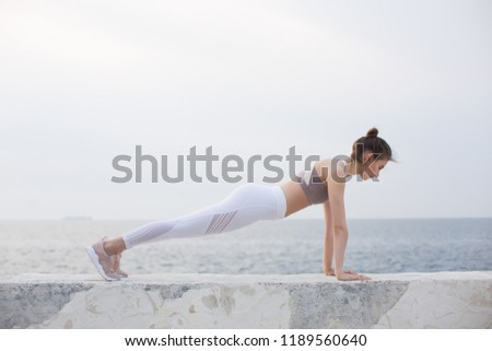 Pretty girl in sporty top and white leggings practicing yoga with amazing sea view on background. Young thoughtful woman training by the sea #1189560640
