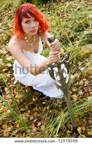Pretty girl in the white dress with vintage sword praying