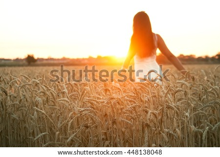 Pretty girl in the yellow wheat field at the sunset of the sunny summer day #448138048