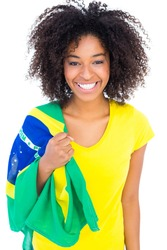 Pretty girl in yellow tshirt holding brazilian flag smiling at camera on white background