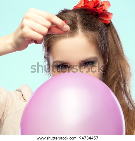 Pretty girl is going to pop a balloon with a pin