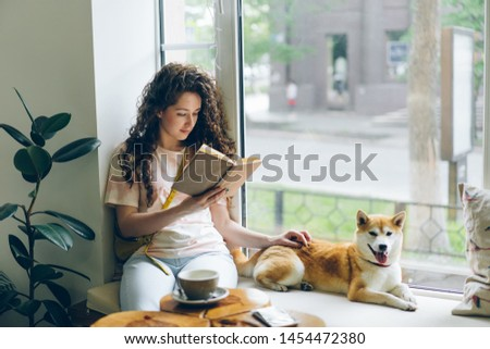 Pretty girl is reading book and stroking shiba inu puppy relaxing on window sill in cafe enjoying leisure time. Hobby, youth and happiness concept.