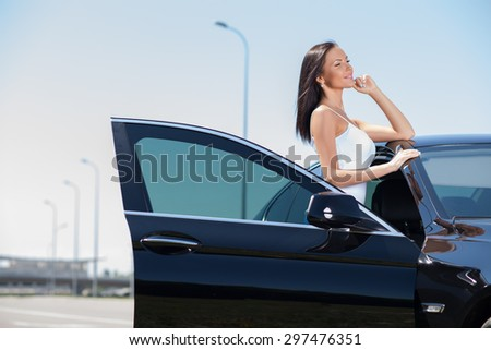 Pretty girl is standing near her car. She is leaning on the roof and is looking aside dreamingly. She is smiling with anticipation. Copy space in left side