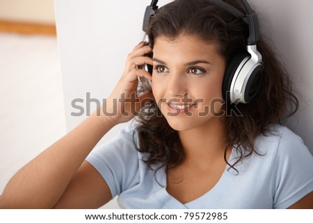 Pretty girl listening music through headphones, smiling, looking away.?