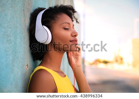 Pretty girl listening music with her headphones in the street #438996334