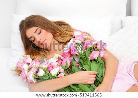 Pretty girl lying in bed with big bouquet of flowers #519411565