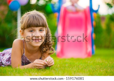 Pretty girl lying on green grass at playground