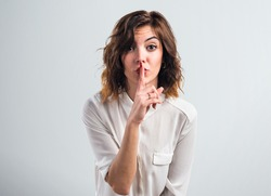 Pretty girl making silence gesture over grey background