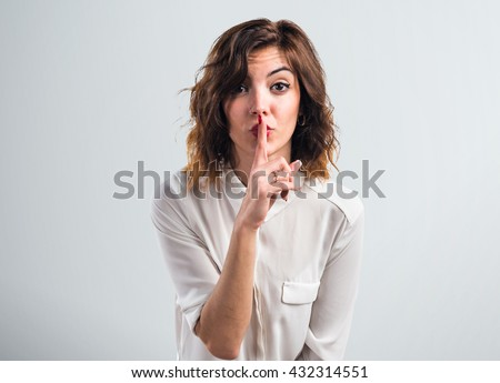 Pretty girl making silence gesture over grey background #432314551