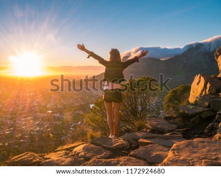 Pretty Girl on the Lions Head Mountain in Cape Town in front of the Table Mountain at Sunrise - South Africa
