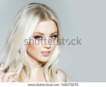 pretty girl or cute sexy woman with long platinum blonde hair and fashionable makeup on face on grey background, copy space