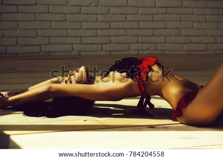 Stock Photo pretty girl or cute woman with long brunette hair in sexy fashionable black and red lace lingerie laying on wood floor on white brick wall background