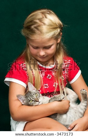 Pretty girl playing with her pet cat.