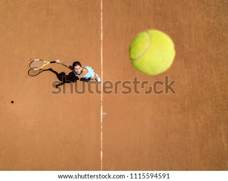 Pretty girl plays tennis on the court outdoors. She prepares to beat on a ball. Woman wears a light blue sportswear with white sneakers. Top view horizontal photo.