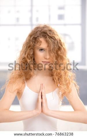 Pretty girl practicing yoga, meditating in prayer pose sitting on floor.?