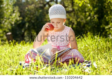 Pretty girl reading a book and eating an apple