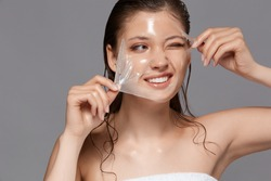 pretty girl removing purifiying facial mask with one eye closed and smile on face, skin treatment with beautiful lady