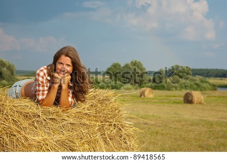 Pretty girl resting on straw bale