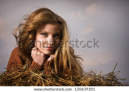 Pretty girl resting on straw bale on the dark sky background