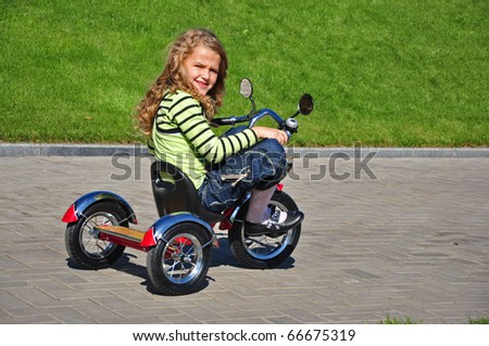 Pretty girl ride on a tricycle