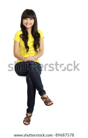 Pretty girl sitting casual on big blank billboard poster sign with lot of copy space